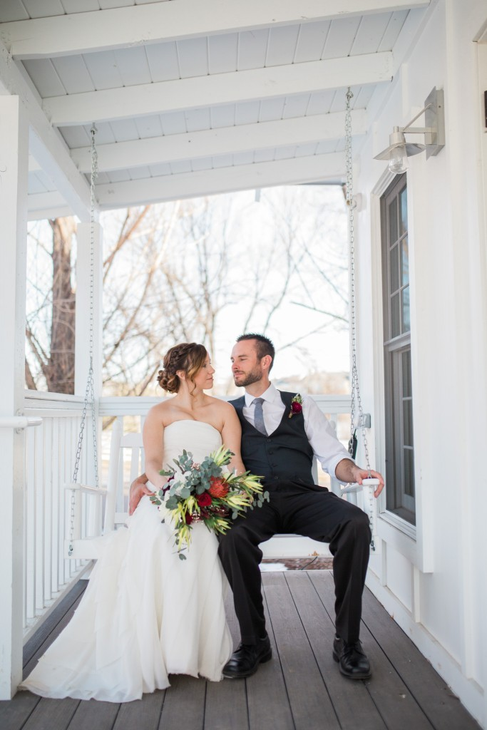 Just married on porch swing at the Barn at Raccoon Creek